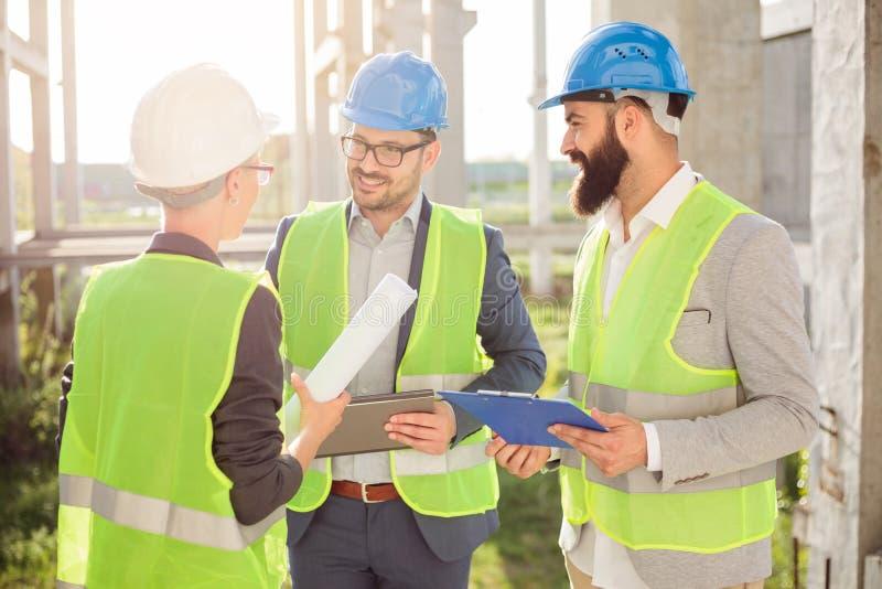 Grupo pequeno de arquitetos que discutem detalhes do projeto e que verificam o progresso de trabalho imagem de stock