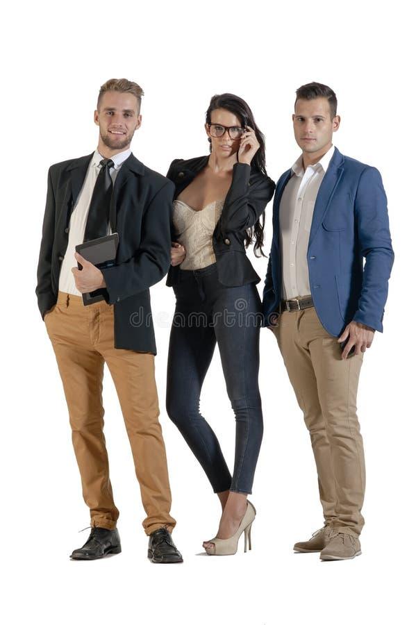 Grupo pequeno de executivos novos que trabalham estar junto imagem de stock
