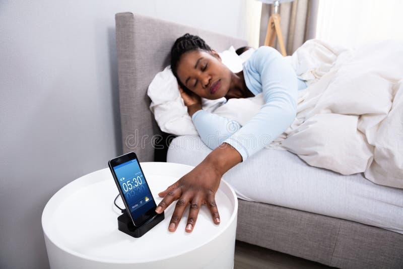 Grupo pr?ximo do alarme do sono da mulher no telefone celular imagem de stock royalty free