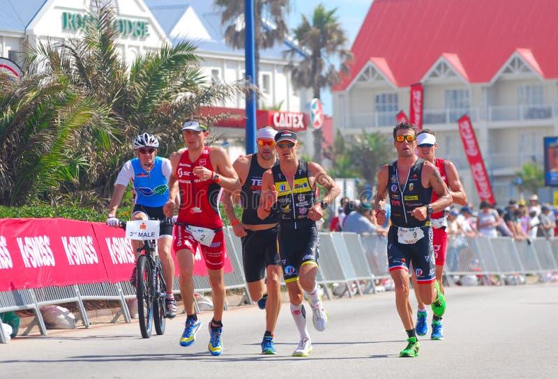 Grupo de funcionamiento profesional de los triathletes de Ironman foto de archivo libre de regalías
