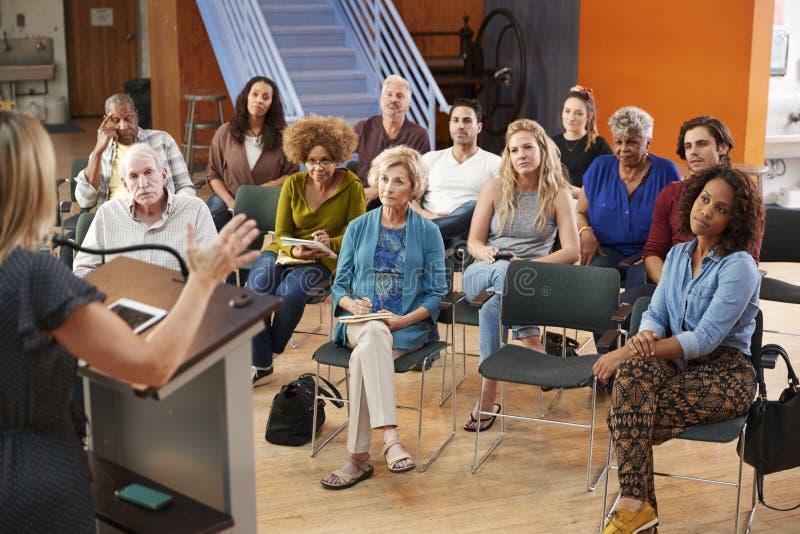 Grupo que assiste à reunião da vizinhança que escuta o orador no centro comunitário fotografia de stock royalty free
