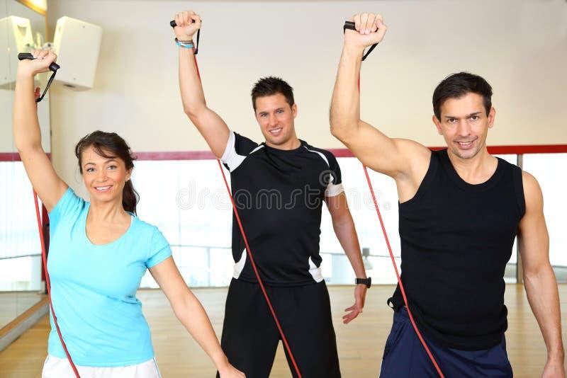 Grupo que elabora em um gym usando expansores imagens de stock