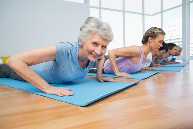 Grupo que hace actitud de la cobra en fila en la clase de la yoga fotografía de archivo