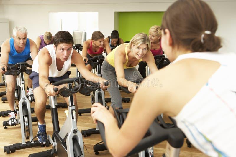 Grupo que participa na classe de giro no Gym foto de stock