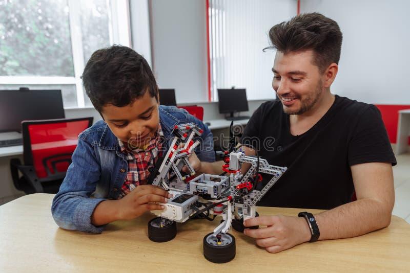 Grupo racial misturado de alunos que controlam a máquina robótico com o professor do controlo a distância junto Mi?dos creativos fotografia de stock