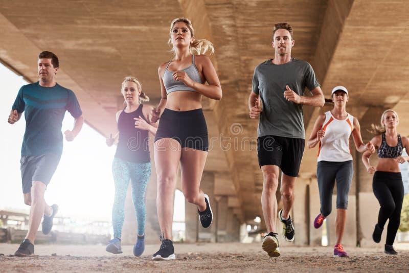 Grupo resuelto de gente joven que corre en ciudad imagenes de archivo