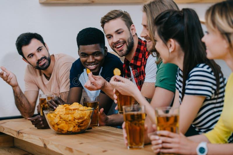 grupo sonriente de amigos multiculturales que comen microprocesadores que bebe la cerveza y que mira el partido de fútbol foto de archivo