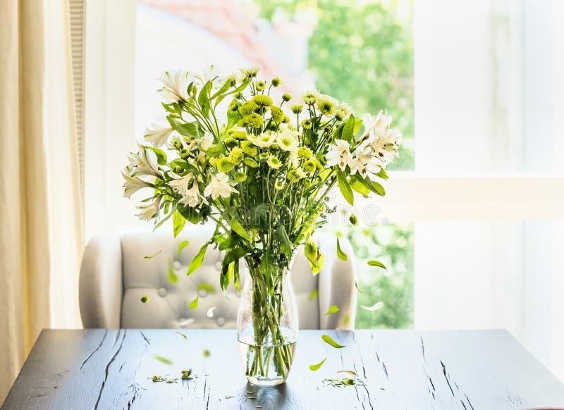 Grupo verde bonito das flores com as pétalas de queda no vaso de vidro na tabela na sala de visitas ensolarada na janela imagem de stock royalty free