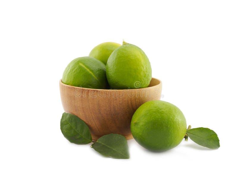 Grupo verde fresco del limón en cuenco de madera en el fondo blanco fotos de archivo