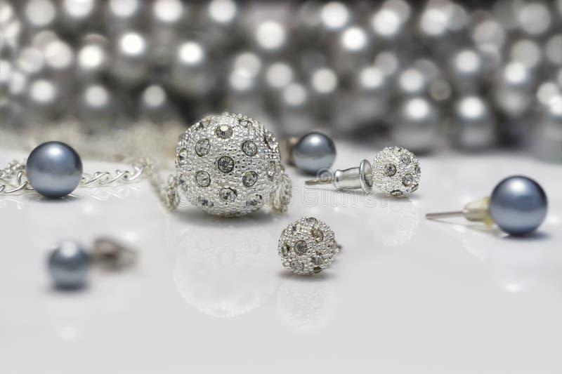 Grupos da joia do close up de brincos enchidos e dos pendentes de prata e pretos das pérolas na placa acrílica fotografia de stock