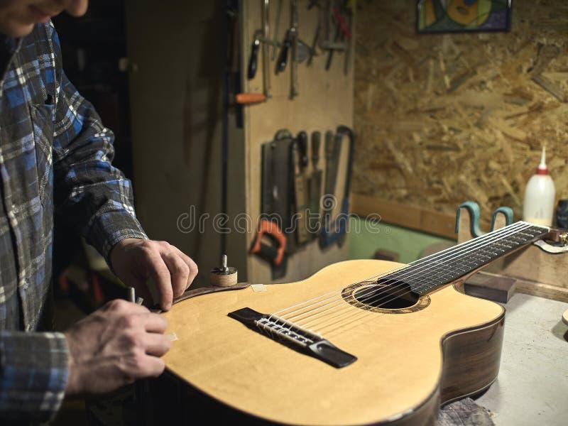 Grupos de Luthiers das guitarra - acima de um suporte sob o braço imagem de stock royalty free