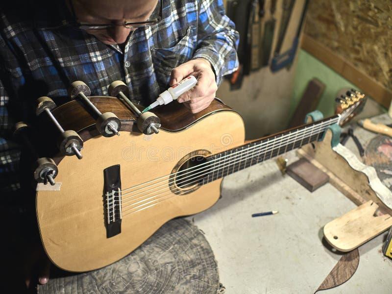 Grupos de Luthiers das guitarra - acima de um suporte sob o braço imagem de stock