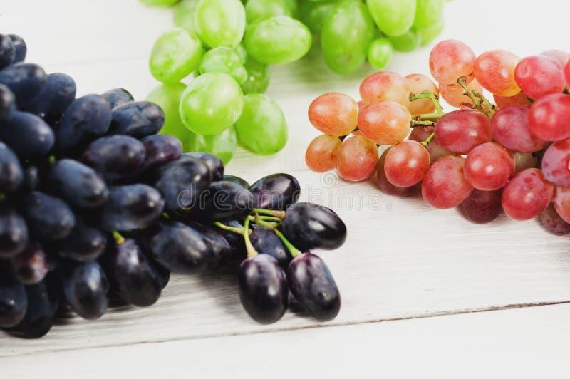 Grupos de uvas azuis e cor-de-rosa e verdes maduras frescas em pranchas brancas de madeira velhas fotografia de stock