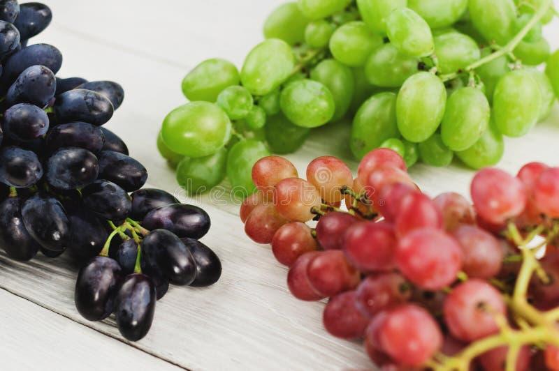 Grupos de uvas azuis e cor-de-rosa e verdes maduras frescas em pranchas brancas de madeira velhas imagem de stock