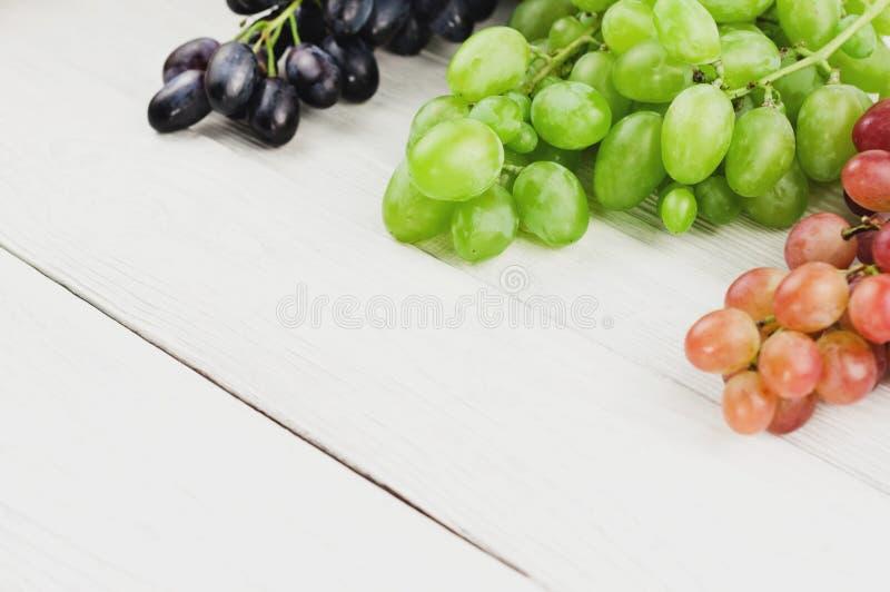 Grupos de uvas azuis e cor-de-rosa e verdes maduras frescas em pranchas brancas de madeira velhas imagens de stock royalty free