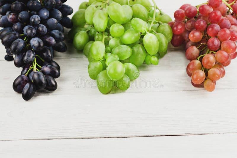 Grupos de uvas azuis e cor-de-rosa e verdes maduras frescas em pranchas brancas de madeira velhas fotografia de stock royalty free