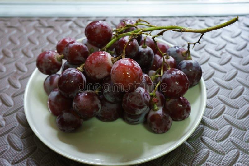Grupos de uvas vermelhas maduras frescas no prato Estilo antigo, um b foto de stock royalty free