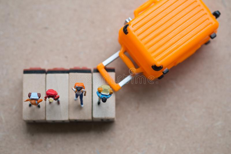Grupowa miniaturowa podróżnika i wycieczkowicza plecaka pozycja na drewnianej etykietce z walizką fotografia royalty free