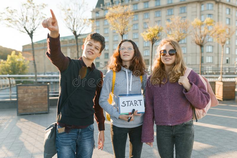 Grupowa nastolatek chłopiec i dwa dziewczyny z notepad z ręcznie pisany słowo początkiem, Nastolatkowie patrzeje naprzód, miasta  obrazy royalty free
