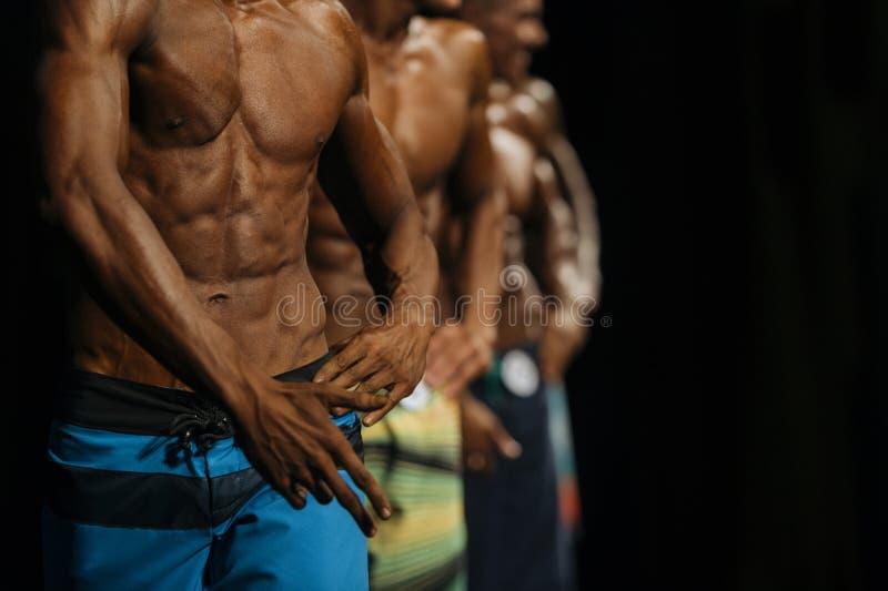 Grupowi atlet bodybuilders w kolorowym lecie zwierają przy competi fotografia royalty free