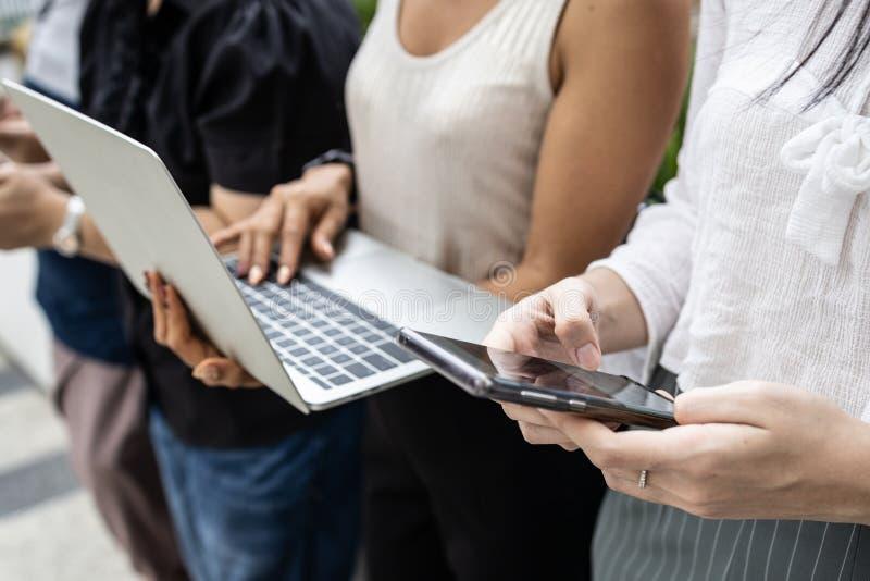 Grupowi azjatykci ludzie używa przyrząda smartphone i laptop obrazy stock