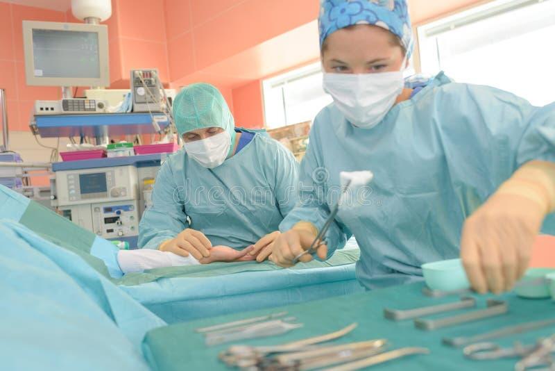 Grupowi chirurdzy działa pacjenta w chirurgicznie theatre zdjęcie stock