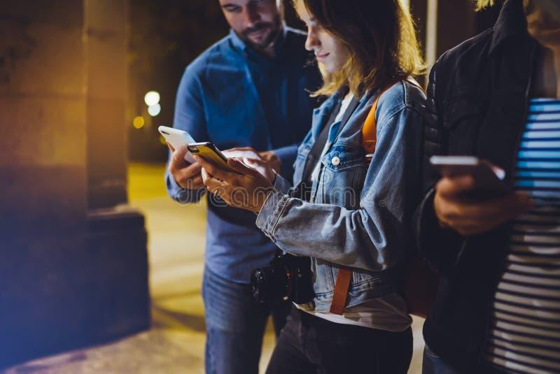 Grupowi dorosli modnisie używa w ręka telefonu komórkowego zbliżeniu, uliczny online fi interneta pojęcie, bloggers przyjaciele w obrazy royalty free