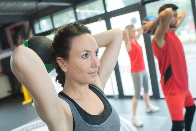 Grupowi ludzie pracujący out trenować z kettlebells w gym zdjęcia stock