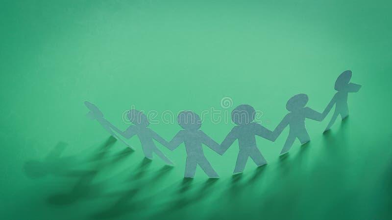 Grupowy papierowy mężczyzna na zielonym tle zdjęcie royalty free