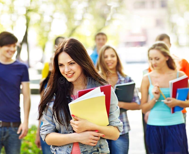 Grupowy uczeń z notatnikiem na ławce plenerowej. fotografia stock