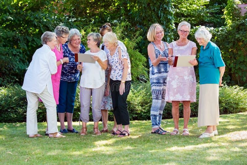 Grupp av äldre damer på ett omsorghem som tycker om stimulerande idérik det fria för en konstgrupp i en trädgård eller att parker royaltyfria bilder
