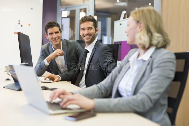 Grupp av affärsfolk i ett modernt kontor som arbetar på datoren royaltyfri bild