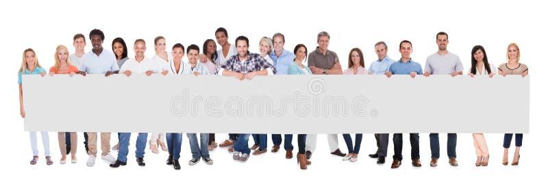 Grupp av affärsfolk med ett tomt baner royaltyfri bild