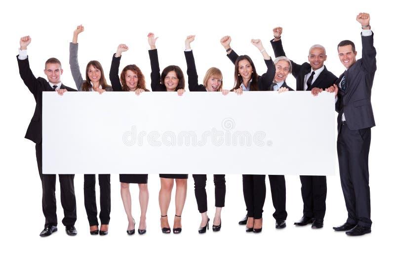Grupp av affärsfolk med ett tomt baner royaltyfria bilder
