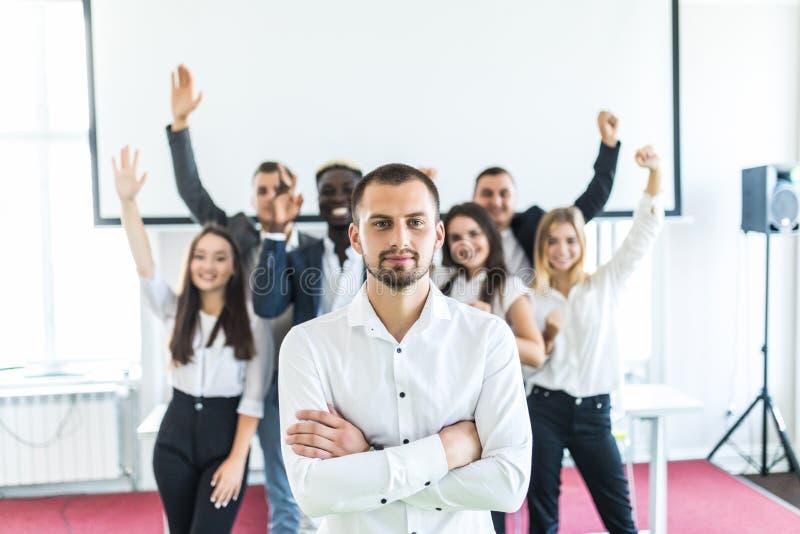 Grupp av affärsfolk med ledaren på framdelen Affärslaget firar uppnådda mål medan ledaren som framme står med korsat arkivbild