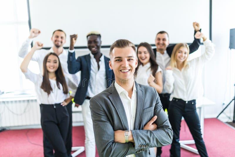 Grupp av affärsfolk med ledaren på framdelen Affärslaget firar uppnådda mål medan ledaren som framme står med korsat royaltyfria bilder