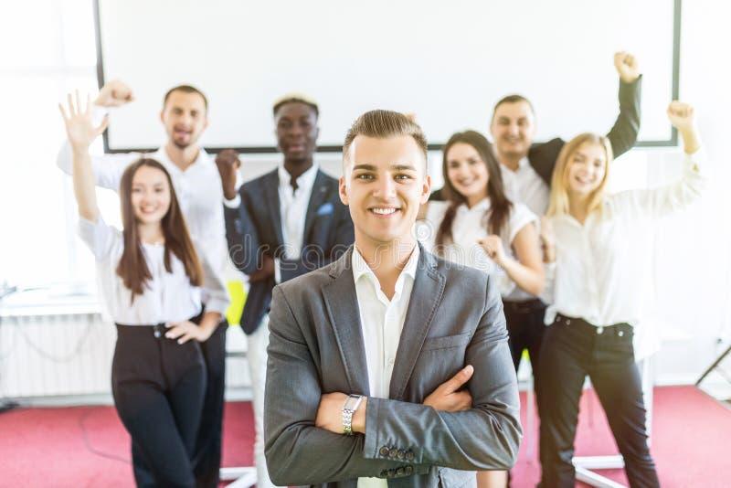 Grupp av affärsfolk med ledaren på framdelen Affärslaget firar uppnådda mål medan ledaren som framme står med korsat royaltyfri bild