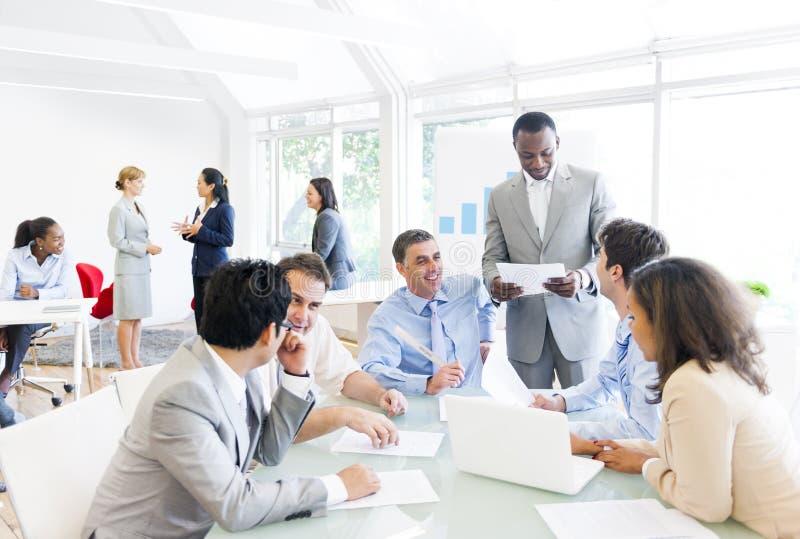 Grupp av affärsfolk runt om konferenstabellen arkivbild