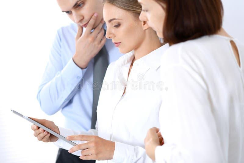 Grupp av affärsfolk som använder bärbar datordatoren, medan stå i regeringsställning Möte- och teamworkbegrepp royaltyfri bild