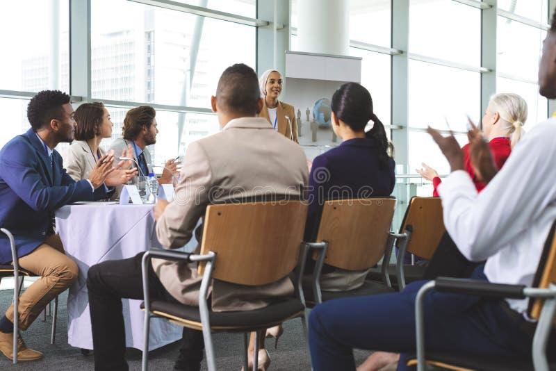 Grupp av affärsfolk som applåderar i ett affärsseminarium royaltyfri bild