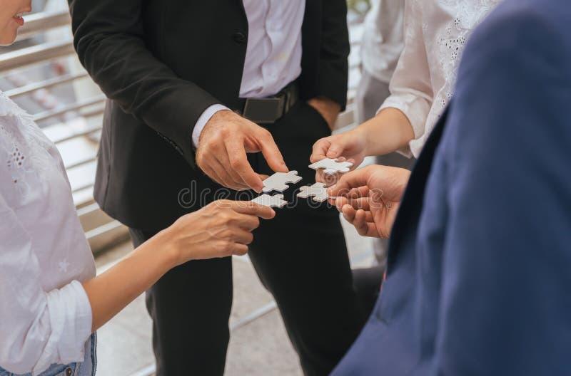 Grupp av affärsfolk som gör figursågen och applicerar som tillsammans förbinder arkivfoton