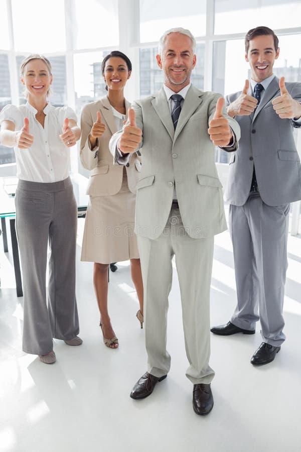 Grupp av affärsfolk som ger upp tummar arkivbild