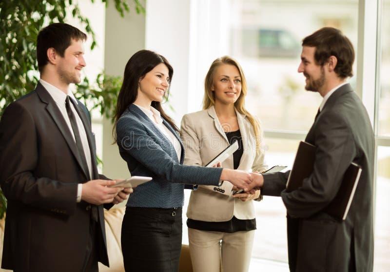 Grupp av affärsfolk som gratulerar deras handshakingkollegor arkivbild