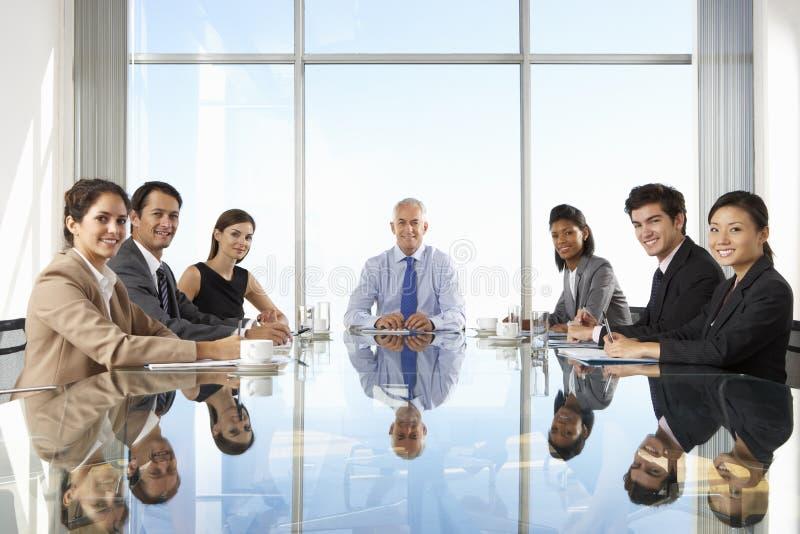 Grupp av affärsfolk som har styrelsemötet runt om den Glass tabellen royaltyfri fotografi