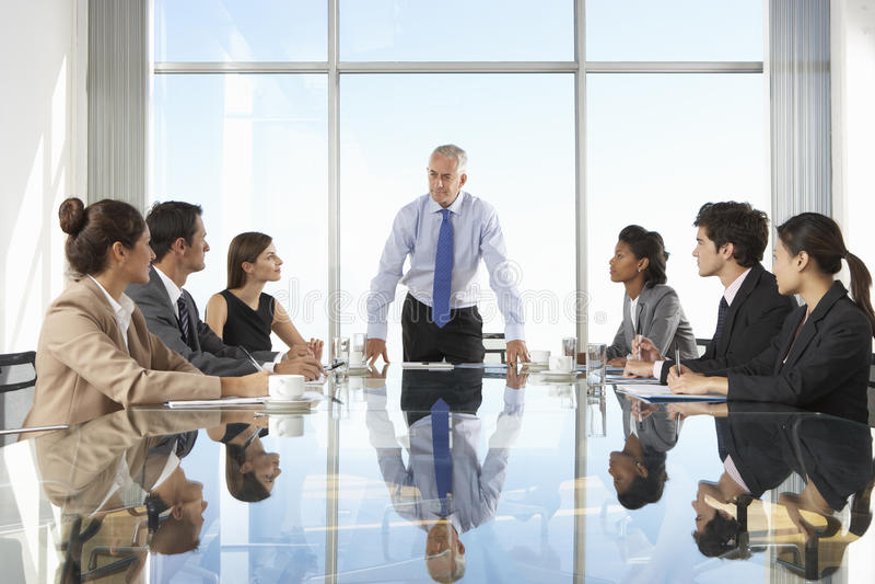Grupp av affärsfolk som har styrelsemötet runt om den Glass tabellen arkivfoto