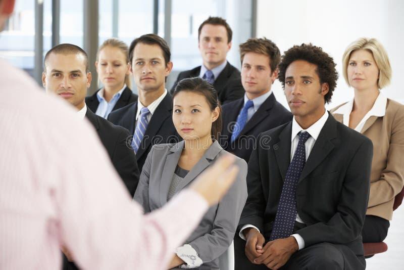 Grupp av affärsfolk som lyssnar till högtalaren som ger presentation arkivfoto