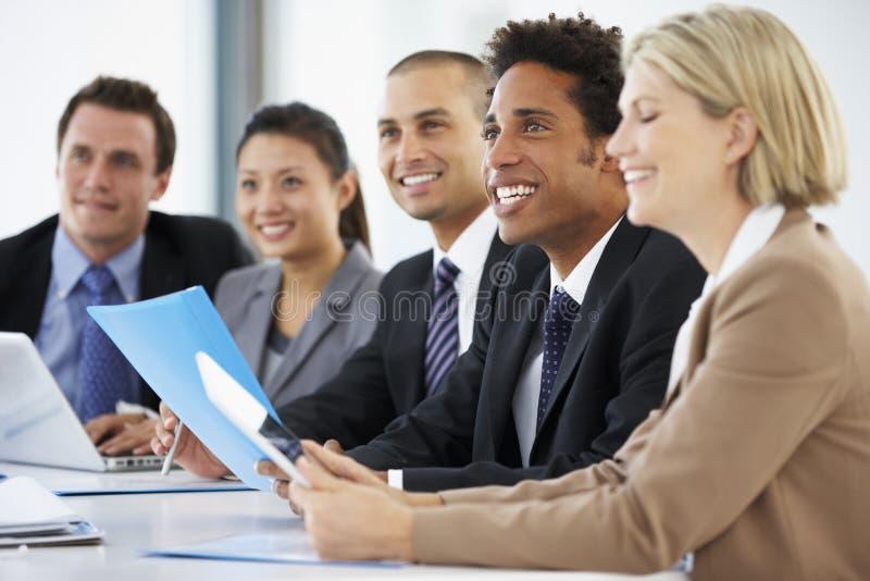 Grupp av affärsfolk som lyssnar till kollegan som tilltalar kontorsmöte royaltyfri fotografi
