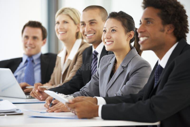 Grupp av affärsfolk som lyssnar till kollegan som tilltalar kontorsmöte royaltyfri foto