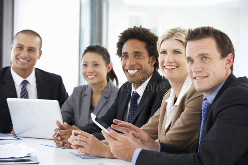 Grupp av affärsfolk som lyssnar till kollegan som tilltalar kontorsmöte arkivbild
