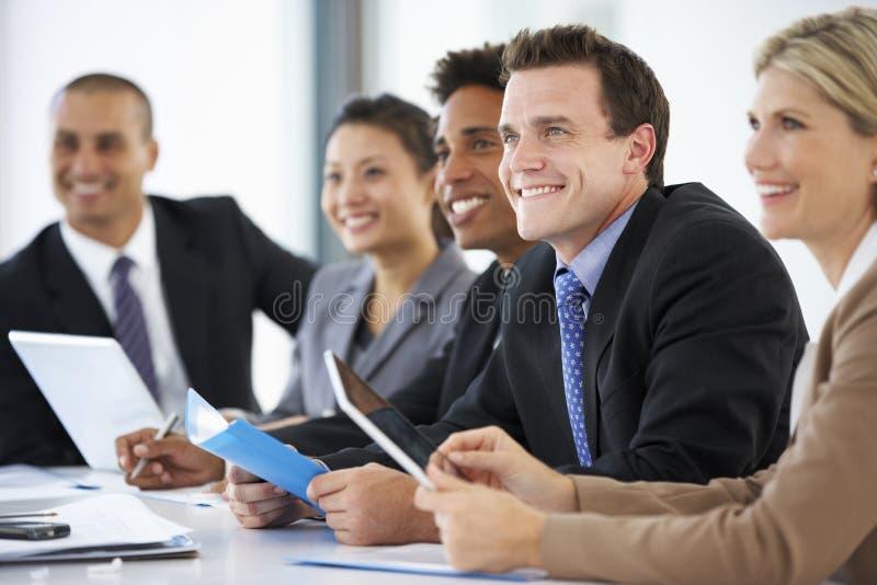 Grupp av affärsfolk som lyssnar till kollegan som tilltalar kontorsmöte royaltyfria bilder